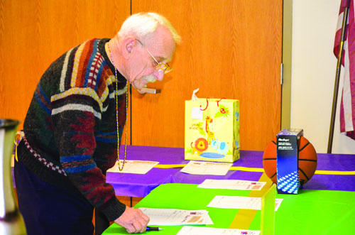 Bruce Rogers checks out items on the silent auction table.